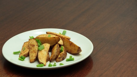 Fresh baked potato wedges sprinkled with spring onion on white plate on wooden table, homemade food, close-up