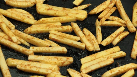 preperation: Uncooked french fries with spices on baking pan