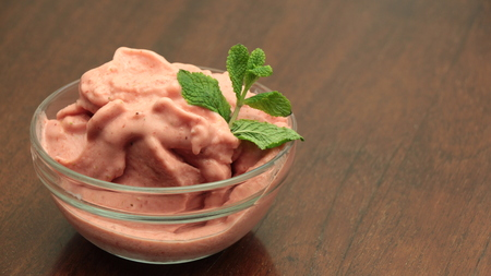 Homemade strawberry ice cream in bowl on wooden surface Stock Photo
