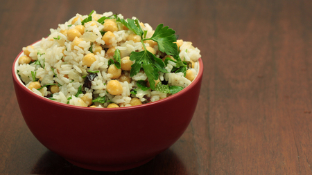 Middle Eastern Rice and Chickpeas Salad in Red Bowl on Wooden Background