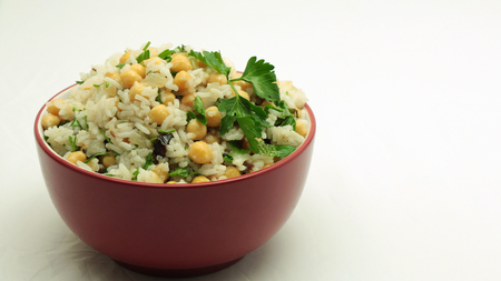 Middle Eastern Rice and Chickpeas Salad in Red Bowl on White Background Stock Photo