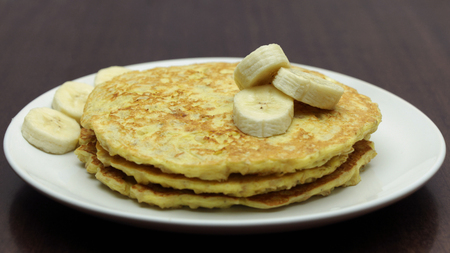 Healthy Pancakes with Banana Slices on White Plate on Wooden Table