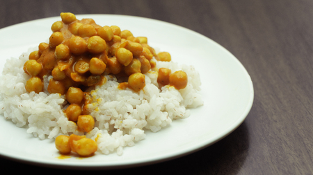 Chickpea Curry with Rice on a White Plate on a Wooden Table