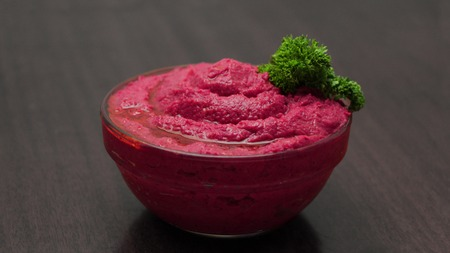 Roasted Beet Hummus in a Glass Bowl on a Wooden Background Stock Photo