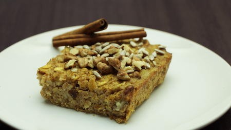 Healthy Baked Oatmeal with Nuts, Seeds and Cinnamon on White Plate on Wooden Background