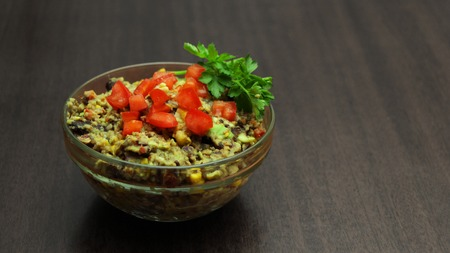 Black Bean and Avocado Dip in a Glass Bowl on Wooden Background. With Bell Pepper, Corn and Parsley.
