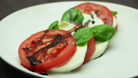 Caprese Salad on a White Plate on Wooden Background