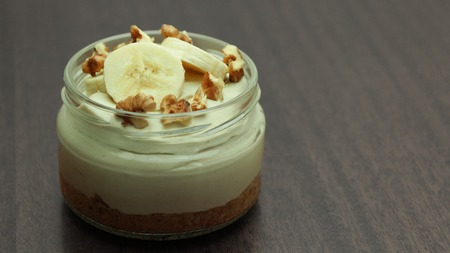 No Bake Banana Cheesecake in Glass Jar on Wooden Background Stock Photo