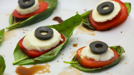 Halloween Caprese Salad with Basil, Mozzarella, Olives, and Balsamic Sauce on a White Background