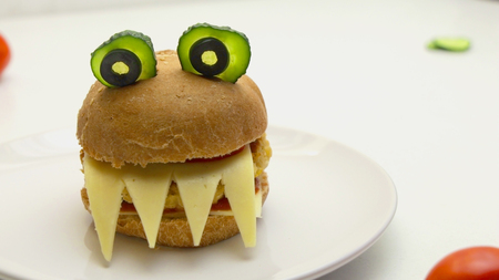 Burgers in the shape of devil with cheese, tomatoes, cucumbers, and olives.