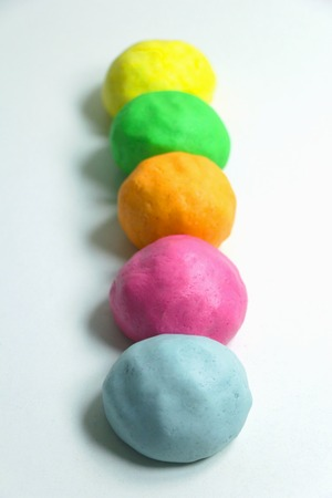 Homemade colorful clay on a white table.
