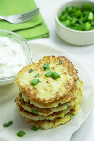 Healthy Veggie Fritters with Greek Yogurt Sauce on a White Plate. Top View