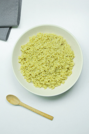 Cooked quinoa in white bowl on white background