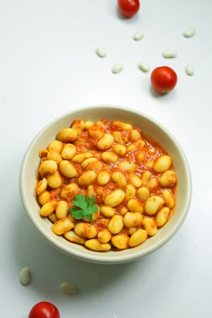 Beans in tomato sauce topped with parsley in a ceramic bowl on a white background