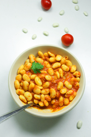 Beans in tomato sauce topped with parsley in a ceramic bowl with metal spoon on a white background