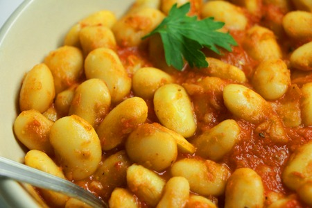 Homemade White Beans in Tomato Sauce topped with Parsley. Close up