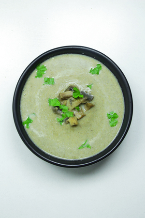 Mushroom cream soup with parsley in a black bowl on a white background Stok Fotoğraf