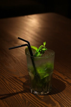Mojito cocktail in a glass on a wooden table. Dark style Stock Photo