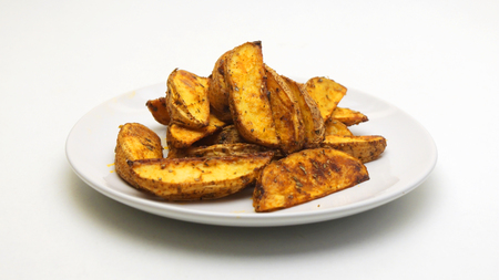 Baked potato wedges on a white background. Healthy food concept. Vegan Stock Photo