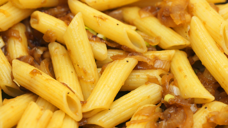 Close up of penne pasta with sauteed onion. Healthy food concept. Vegan Stock Photo