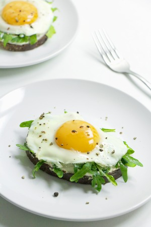 Open-Faced Sandwiches with Ricotta, Arugula, and Fried Egg on a White Plate. Healthy Food