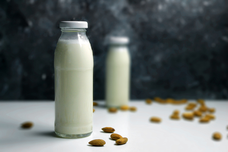 Almond milk with almond on a white table. Plant based recipe