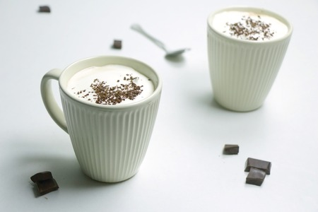 Homemade Hot Chocolate Drink topped with Whipped Cream and Grated Chocolate in a White Mug on a White Background