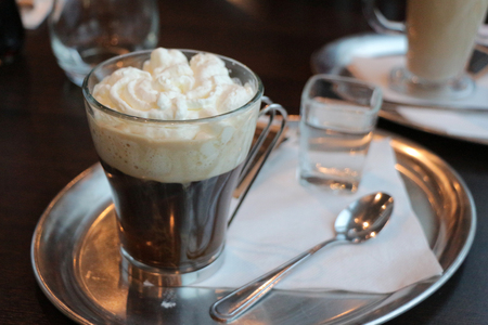 Viennese coffee. Vienna coffee topped with whipped cream with glass of water and metal spoon on a metal tray on a wooden table.