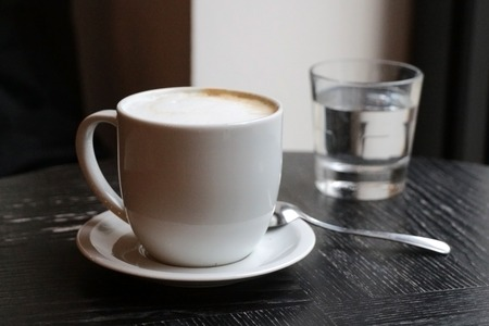 Latte coffee in a white cup on old wooden table with glass of water and spoon. Stock Photo