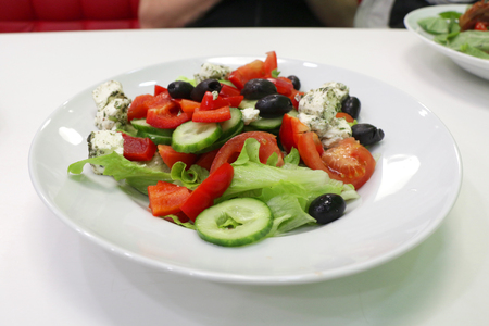Greek salad of fresh cucumber, tomato, sweet pepper, lettuce, red onion, feta cheese and olives with olive oil in a white plate on a white table. View from above. Stock Photo