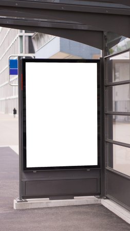 Blank white mock up of vertical light box in a bus stop.Mock up of a billboard. Poster on street at sunny day.