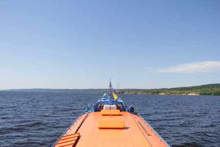 Forward view from a motorboat. Orange motor boat sailing on a sunny day. Stock Photo