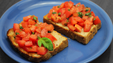Bruschetta with fresh tomatoes and green basil on a blue plate on a wooden background. Healthy Italian food. Stock Photo