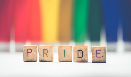 Pride sign made with colorful wooden alphabet letters on a pride LGBT rainbow flag background. Stock Photo