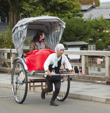 rikscha: Osaka, Japan - 3. November: Touristen reiten eine Rikscha in Arashiyama, ein Touristenzentrum in Kyoto am Nov 3, 2014 Rickshaw eine beliebte Art der Fortbewegung in Japan im 19. Jahrhundert. Rikscha