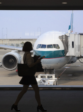 Osaka, Japan - Nov 7: Silhouette of a businesswoman boarding a Cathay Pacific passenger airplane in the Kansai International Airport in Osaka, Japan on Nov 7, 2014. Cathay Pacific is an international airline based in Hong Kong. It provides passenger and c Editorial