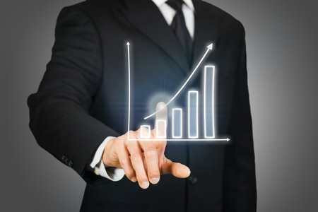 touchscreen: Businessman clicking on a rising chart on a virtual touchscreen Stock Photo
