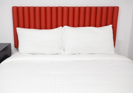 headboard: Bed with headboard and pillows in a hotel room