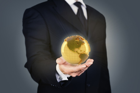 Composite image of a businessman holding a golden globe photo
