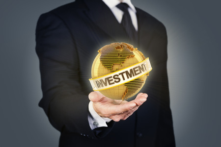 golden globe: Composite image of a businessman holding a golden globe with investment text