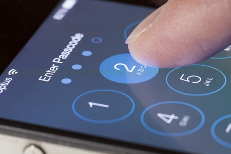 Adelaide, Australia - September 20, 2013: Entering passcode on an iPhone running iOS. iOS is the foundation of iPhone, iPad, and iPod touch. It comes with a collection of apps and useful features. The iOS 7 update features a redesigned interface and hundr Publikacyjne