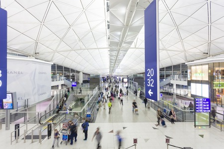 Hong Kong, China - November 29, 2013: Travellers walking in the Hong Kong International Airport. The airport is one of the worlds busiest passager airports, and is an important gateway for destinations in Mainland China and other parts of Asia.