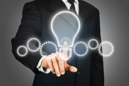 clicking: Businessman clicking a virtual light bulb and gears Stock Photo