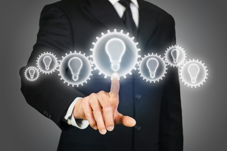 clicking: Businessman clicking on a virtual touchscreen with gears with light bulb