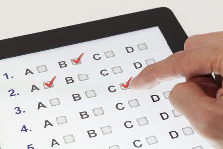 evaluacion: Clic dedo en una tablilla con preguntas de opción múltiple Foto de archivo