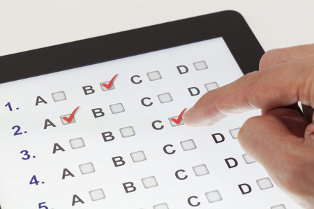 online form: Finger clicking on a tablet with multiple-choice questions