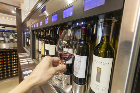 dispense: Adelaide, Australia - March 14, 2015: Tourist filling a glass with red wine for wine tasting inside a the National Wine Centre of Australia in Adelaide.