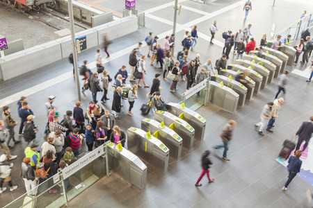 train ticket: Melbourne, Australia - April 2, 2015: People passing through the gates at the Southern Cross Station in Melbourne, Australia. It is a major railway station in Melbourne.