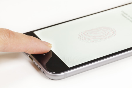 fingerprint: Melbourne, Australia - April 22, 2015: Using the Touch ID on an iPhone 6. Touch ID is a fingerprint recognition feature designed by Apple Inc.