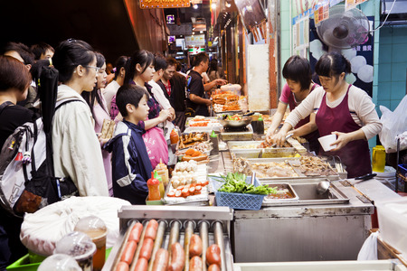 Hong Kong, China - November 16, 2011: Food vendors in Mong Kok, Hong Kong, selling street food for take away. These vendors offer some great street food, including fish balls, octopus legs, pig skin, red sausage.
